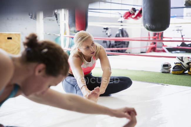 Молодые женщины растягивают ноги рядом с боксерским рингом в спортзале — стоковое фото