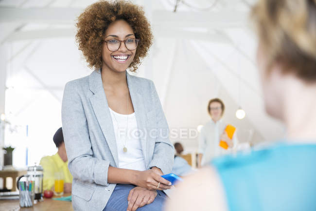 Holding smart phone and smiling in office,Portrait of woman wearing spectacles — Stock Photo