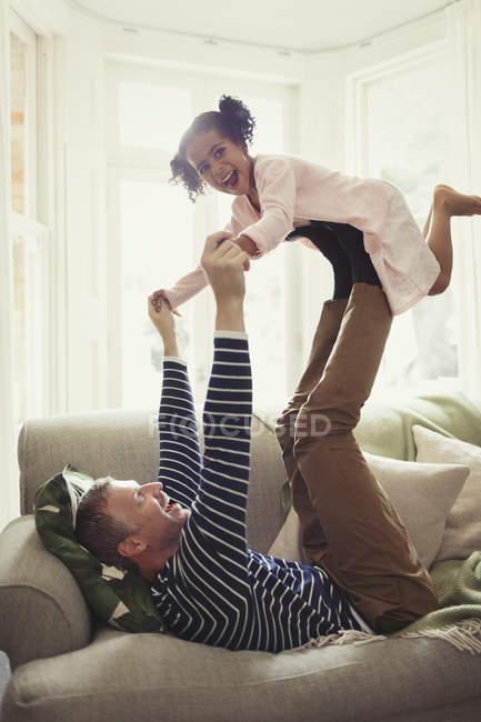Multiétnico juguetón padre hija equilibrio en patas arriba en el sofá - foto de stock