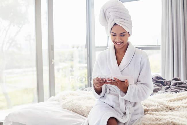 Улыбающиеся женщина в халат и волос, завернутый в полотенце, используя цифровой планшет на кровати — стоковое фото