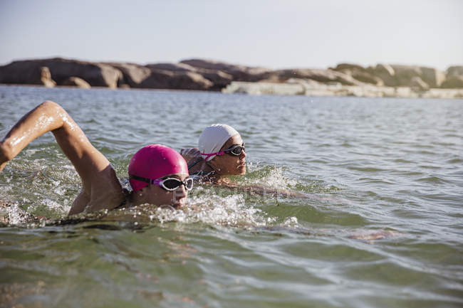 Female active swimmers at ocean against shore during daytime — Stock Photo