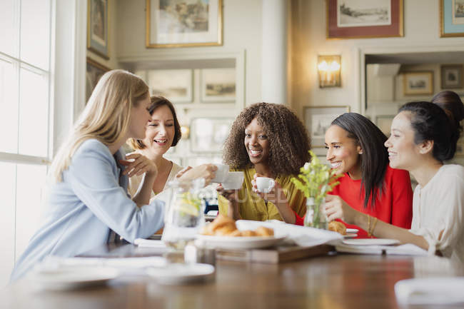 Smiling women drinking coffee and talking at restaurant table — Stock Photo