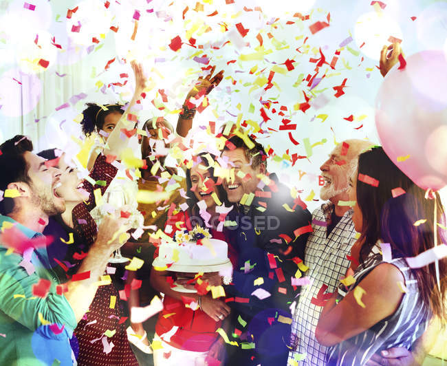 Family throwing confetti celebrating birthday party with cake — Stock Photo
