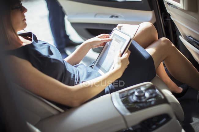 Empresária usando tablet digital no banco de trás do carro — Fotografia de Stock
