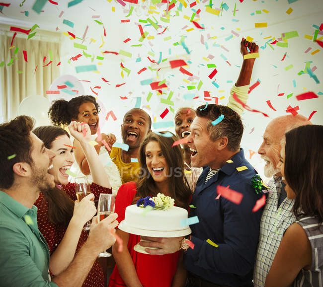 Enthusiastic family with birthday cake throwing confetti — Stock Photo
