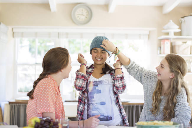 Three teenage girls playing with beanie in dining room — Stock Photo