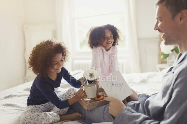 Daughters serving coffee and card to father in bed on Fathers Day — Stock Photo
