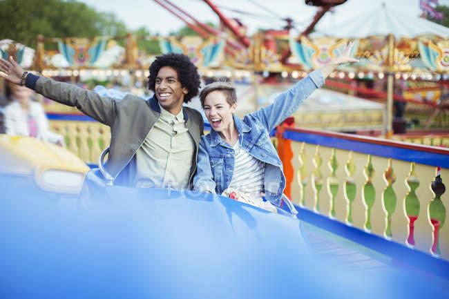 Couple gai sur carousel en parc d'attractions — Photo de stock