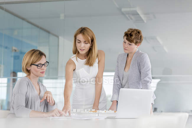 Female architects discussing blueprint at laptop in conference room meeting — Stock Photo