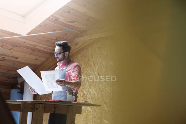 Artist reviewing drawings in modern art studio — Stock Photo