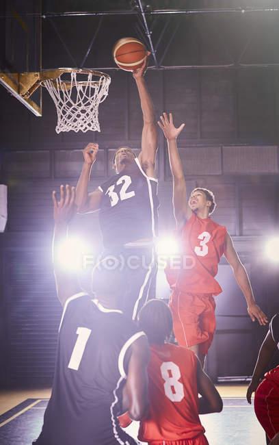 Giocatori di basket maschile giovane giocando a basket in palestra — Foto stock