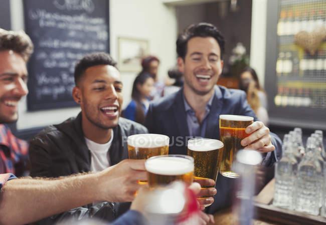 Amigos homens, brindando a copos de cerveja no bar — Fotografia de Stock