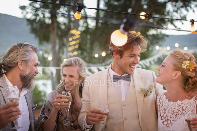 Молодая пара и их гости с шампанским флейты во время свадебного приема в саду — стоковое фото
