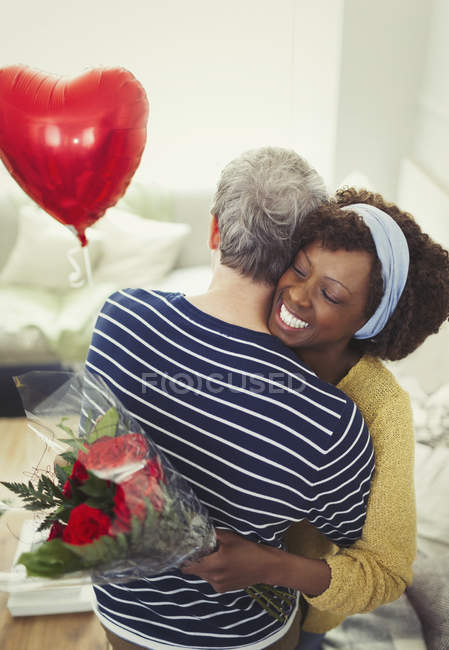 Esposa recibiendo el día de San Valentín rosa bouquet y globo, abrazando a marido - foto de stock