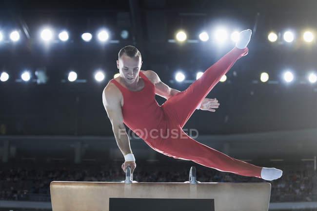 Мужчина гимнаст, выступающий на Поммельской лошади на арене — стоковое фото