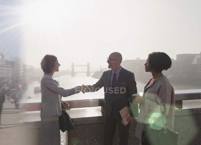 Des hommes d'affaires de Silhouette serrent la main sur un pont urbain ensoleillé au-dessus de Thames River, Londres, Royaume-Uni — Photo de stock