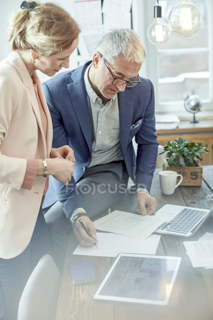 Business people planning, reviewing paperwork at digital tablet in meeting — Stock Photo