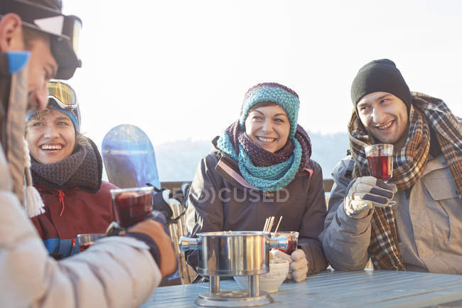 Snowboarder friends drinking cocktails on sunny patio apres-ski — Stock Photo