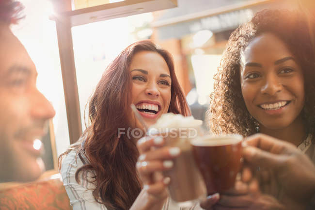 Enthusiastic friends toasting coffee cups at cafe — Stock Photo