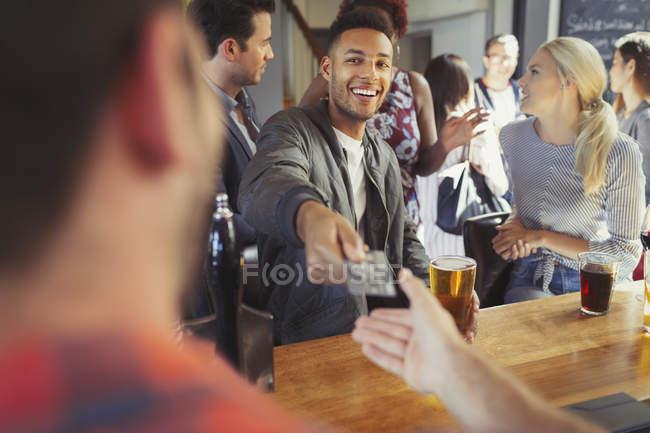 Homem sorridente pagando bartender com cartão de crédito no bar — Fotografia de Stock
