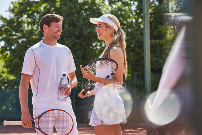 Smiling male and female tennis players talking and holding rackets on sunny tennis court — стоковое фото