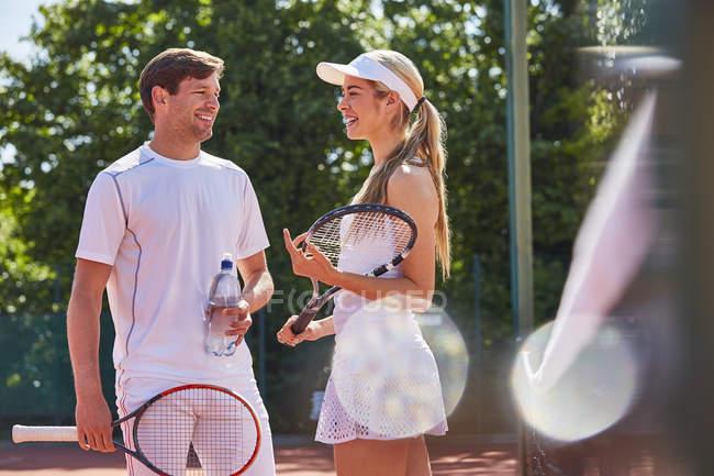 Sonriendo a los jugadores de tenis masculinos y femeninos hablando y manteniendo raquetas en tenis soleado - foto de stock