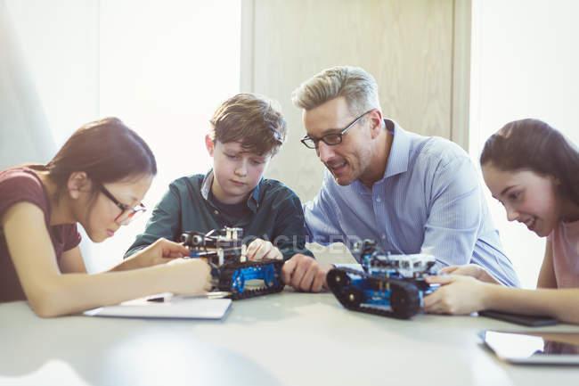 Insegnante maschio aiutando gli studenti montaggio robotica in aula — Foto stock