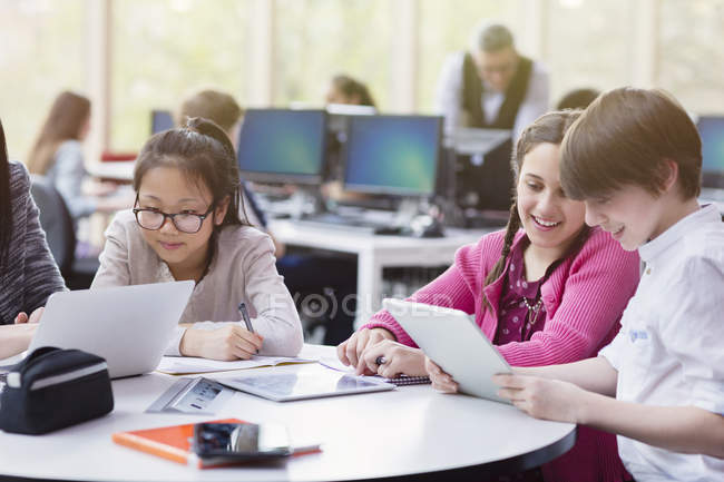Students using digital tablet and laptop in library — Stock Photo
