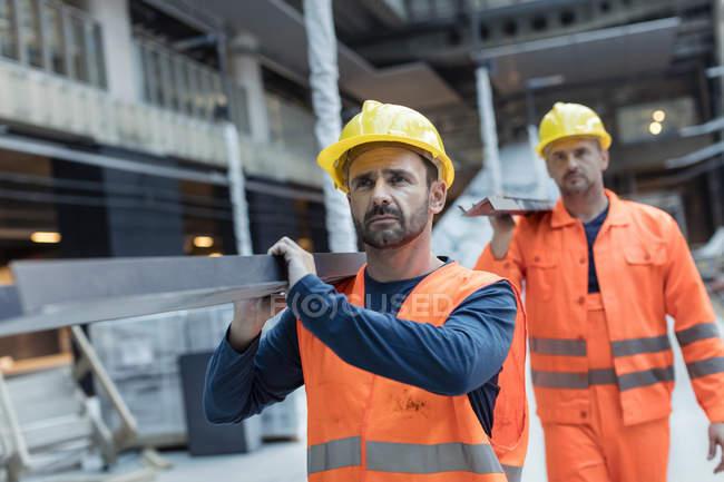 Строительные рабочие, перевозящих металла на строительной площадке — стоковое фото