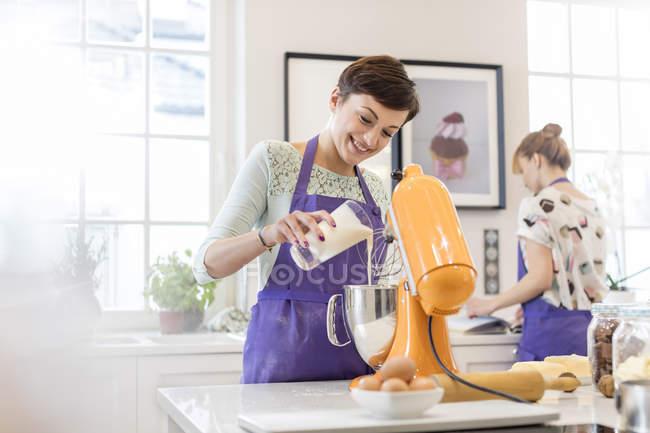 Cuisson de traiteur femelle, en utilisant le mélangeur de stand dans la cuisine — Photo de stock