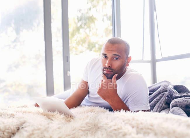 Portrait homme beau sérieux utilisant tablette numérique sur le lit — Photo de stock