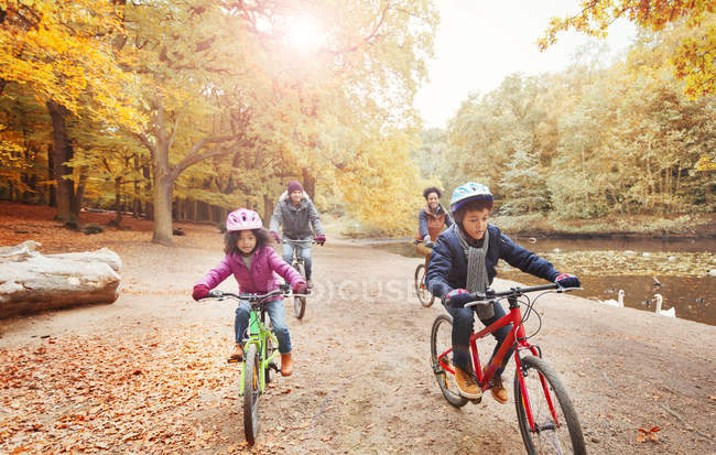 Young family bike riding along pond in autumn park — Stock Photo