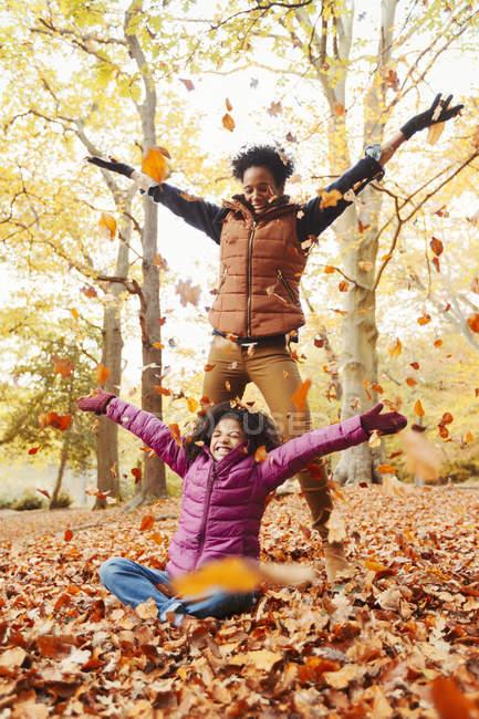 Juguetona madre e hija lanzando hojas de otoño en el parque - foto de stock
