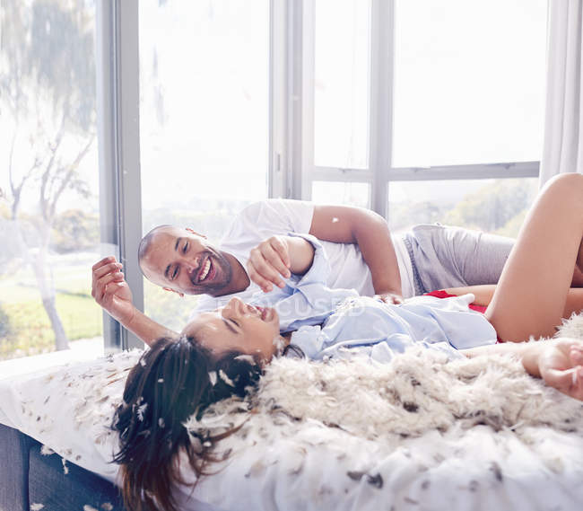 Plumas de almohada pareja juguetona luchando en dormitorio - foto de stock