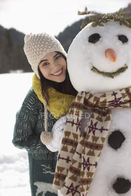 Portrait de femme souriante avec bonhomme de neige — Photo de stock