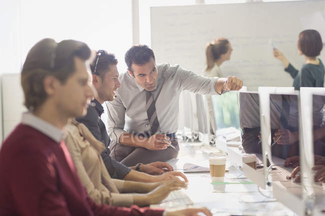 Male supervisor talking with telemarketer at computer in office — Stock Photo