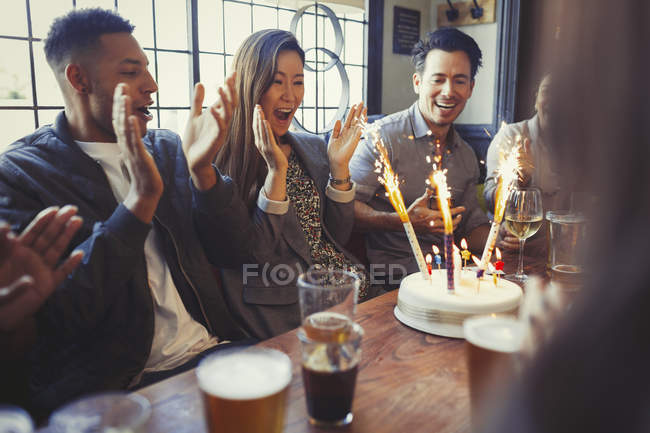 Friends cheering for woman celebrating birthday with fireworks cake at table in bar — Stock Photo