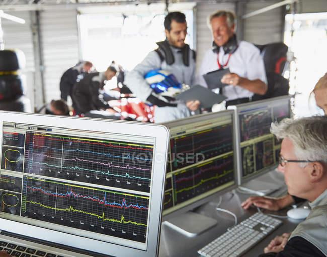 Formel-1-Rennstall überprüft Diagnose an Computern in Reparaturwerkstatt — Stockfoto