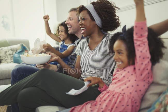 Begeisterte multi-ethnischen junge Familie jubeln, Sportübertragungen auf sofa — Stockfoto