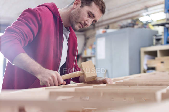 Male carpenter using wood mallet on boat in workshop — Stock Photo