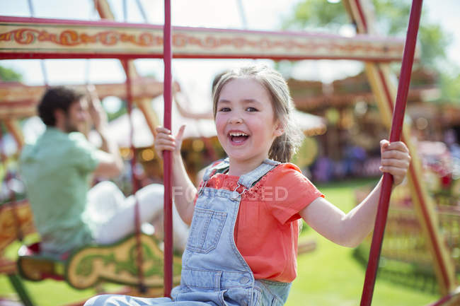 Cheerful girl laughing on carousel in amusement park — Stock Photo