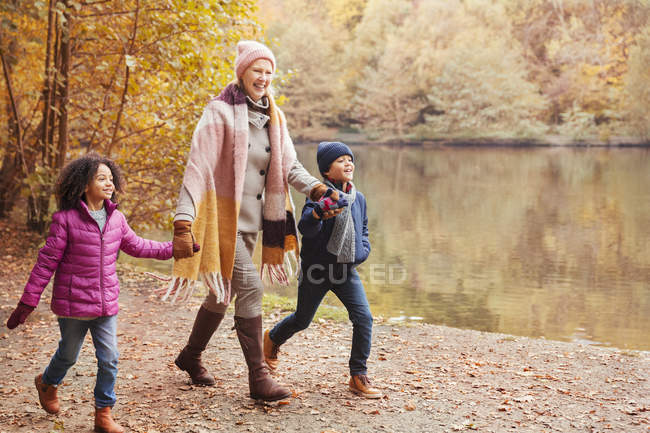 Grandmother holding hands with grandchildren walking along pond in autumn park — Stock Photo