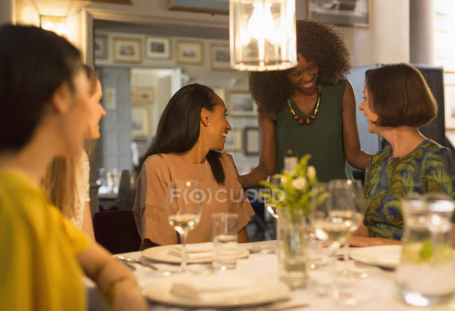 Smiling women friends dining and talking at restaurant table — Stock Photo