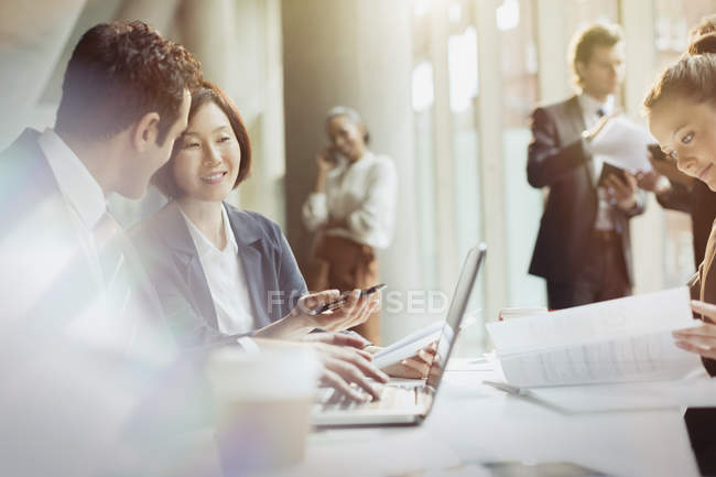 Business people working at laptop in meeting — Stock Photo