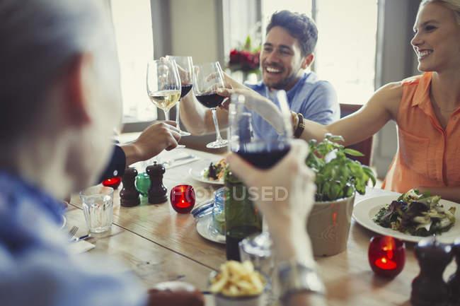 Amigos sorridentes comemorando, brindando com taças de vinho na mesa do restaurante — Fotografia de Stock
