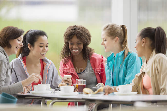 Smiling women friends drinking coffee and using cell phone post workout — Stockfoto