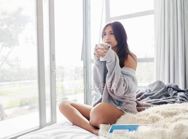 Serene woman drinking coffee on bed — Stock Photo