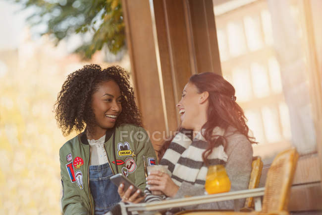 Laughing young women friends with cell phone at urban sidewalk cafe — Stock Photo
