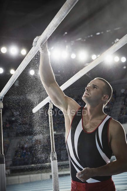 Male gymnast applying chalk powder to parallel bars in arena — Stock Photo