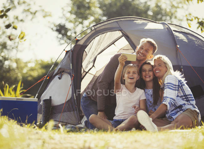 Family taking selfie with camera phone outside tent at sunny campsite — стокове фото